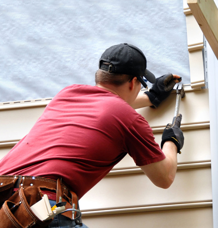 A roofer installing siding on a house