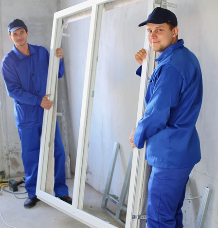 Two workers replacing a window frame.